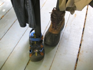 Closeup of the chair feet, in Keene walking sandals and hiking boots.
